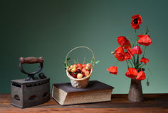 Red poppies in a ceramic vase, books, cherries and old flatiron Royalty Free Stock Photo