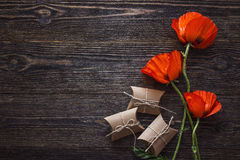 Red poppies flowers with gift boxes on dark wood background. stock photo