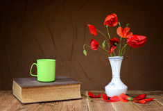 Red poppies, pot and book Stock Photos