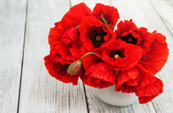 Red poppies in a vase. On a wooden table Royalty Free Stock Images