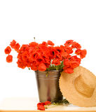 Red poppy flowers in metallic bucket and straw hat Stock Photo