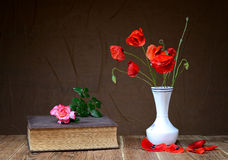 Red poppy in a vase and roses on a book Royalty Free Stock Images