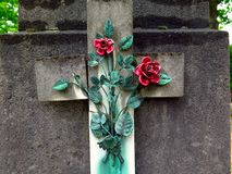 Red porcelain roses on a grave. Two enamelled porcelain roses one of which is broken with oxidized copper rods and leaves. Detail of an old tomb photographed at Stock Image