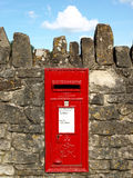 Red Post Box. Traditional British red post box mounted into a wall Stock Photos