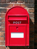 Red post box. A red metal postal box against a background of a brick wall Stock Images