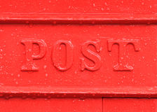 Red Post Box detail. Old English red mailbox detail in the rain showing water drops and the word post Stock Image