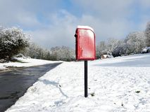 Red post box, Dog Kennel Lane, Chorleywood in winter snow stock image