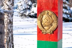 Red post with the emblem of the USSR stands on the border. In the forest stock photography