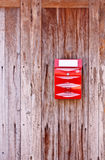 A red postbox. Hanging on old wooden wall Stock Photos