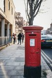 Red postbox belonging to Royal Mail on a street in London, UK stock image