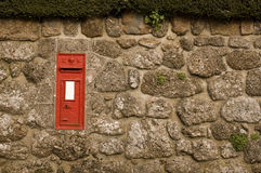 Red Postbox in English Village Wall. Traditional British red postbox in English village wall (Chagford, Devon Royalty Free Stock Photography
