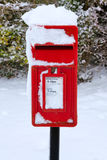 Red postbox in the snow. A traditional red English postbox at winter time covered in snow Royalty Free Stock Photo