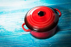 Red pot on blue wooden table Royalty Free Stock Images