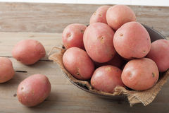 Red potatoes in a bowl on wooden background Stock Images