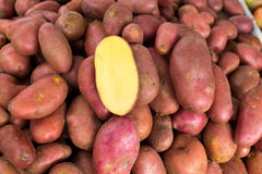 Red potatoes in a market display with half cutted Stock Image