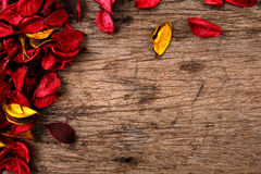 Red potpourri flower petals on wooden background Royalty Free Stock Photo