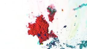 Red powder inks floating on milky liquid. Dry paints moving chaotically on liquid white background. stock photo