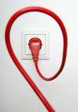Red power cable. Plugged in electric outlet, on white background Stock Photos
