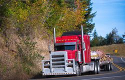 Red powerful big rig semi truck and step deck trailer with cargo Stock Images