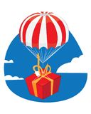 Red present with a blank tag landing with a parachute Stock Photography