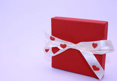 Red present box. With white stripe and hearts Royalty Free Stock Photos