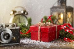 Red present box candle and retro camera with snow Christmas comp Royalty Free Stock Photos