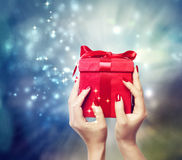 Red present box held up by in a woman's hands Stock Photos