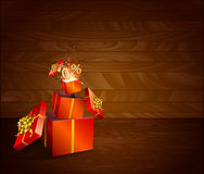 Red present box inside present box on wooden background. Royalty Free Stock Images