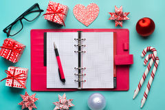 Red present box and paper note with Merry christmas message: Ho Ho Ho! place on office table with laptop, colorful diary and a cup Royalty Free Stock Image