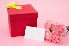 Red present box and pink carnations with a blank card Stock Images
