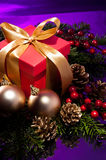 Red present box in a purple Christmas setting Royalty Free Stock Photos