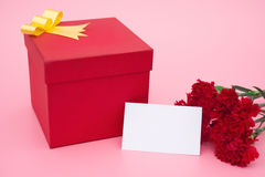 Red present box and red carnations with a blank card Stock Photo