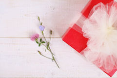 Red present box with white Ribbon on white wooden background . Gift box packaging. Birthday, New year, Valentine's Day, 8 march Royalty Free Stock Photography