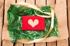 Red present lying on green plastic with golden ribbon string around it, as seen from above Stock Photos