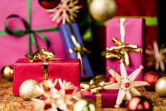 Red Present among other Gifts and Baubles. Crimson gift box with golden bow between baubles and straw stars. Five more single-colored packets out of focus Stock Image