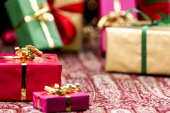 Red Present Among Other Gifts and Baubles. Golden bow knot around a red gift in focus. Blurred shapes of other plain presents in gold, green and magenta outside Stock Photos