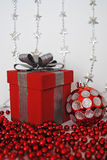 Red present. With a silver bow, silver stars, Christmas bauble and red beads Stock Images