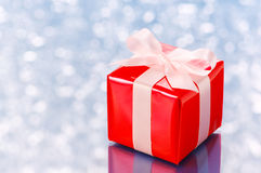 Red present on white sparkle background. Royalty Free Stock Image