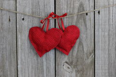 Red printed hearts hanging by ribbons on clohtesline with wood background Royalty Free Stock Photo
