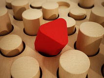 Red prism wooden block standing out among wooden cylinders. 3D illustration Stock Photography