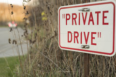 Red private drive sign with car passing in background Stock Photos