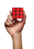 Red Problem solving puzzle cube. White male Caucasian hand holds up a problem solving cube with all red squares stock image