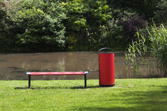 Red public bench and garbage bin. Red public bench and garbage can in grass near water Royalty Free Stock Image
