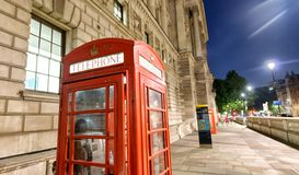 Red public phone booth in London at night near Westminster, UK Royalty Free Stock Images