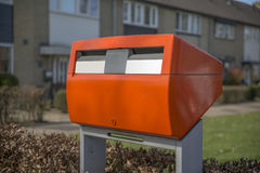 Red public postbox. A red shiny and public postbox in a residential area in the Netherlands Royalty Free Stock Images