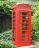 Red Public Telephone. Red public phone on a quiet garden Stock Images