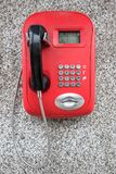 Red public telephone with black handset on the granite wall Stock Photography