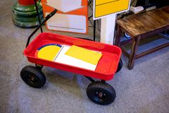 Red pull along wagon cart with black handle and wheels parked  Stock Photography