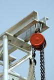 Red pulley. A red pulley and hook with scaffolding against a blue sky Royalty Free Stock Photography