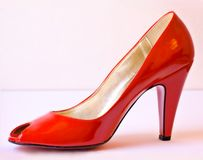 Red Pump. Ladies glamorous vibrant red pump shoe with soft pink background Royalty Free Stock Photo